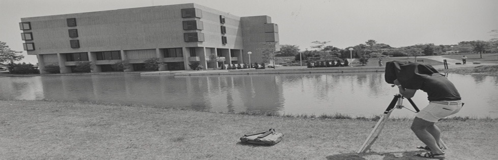 Student taking a photo of Zumberge library and pond